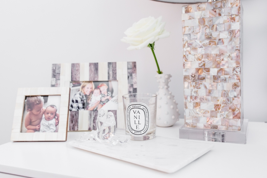 Fashionable Hostess Bedside Table - Diptyque candlye and picture frames