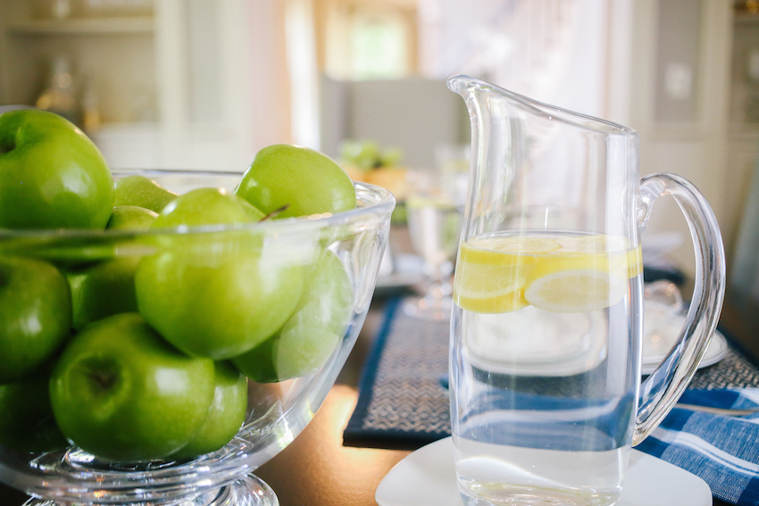 Fresh Lemon Water and Bowl of Apples in Simon Pearce Glass Bowl by Fashionable Hostess