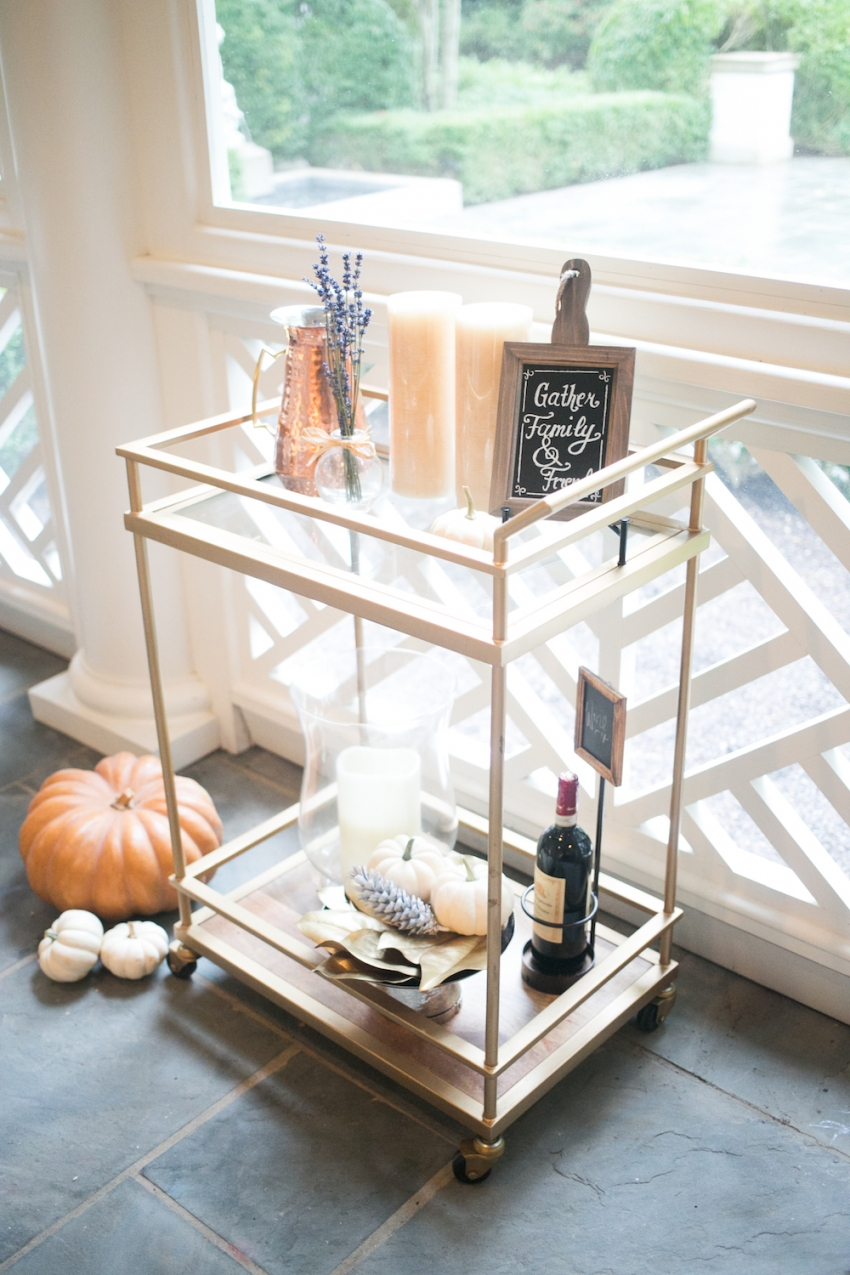 Candles, Red Wine, Pumpkins, and Chalk Board on Bar Cart on Fashionable Hostess