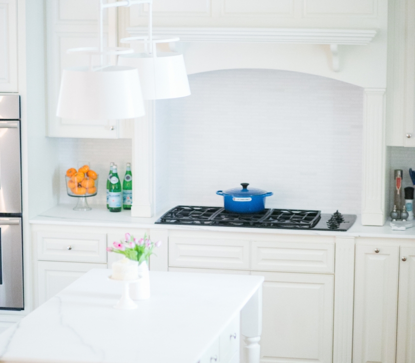 All White Kitchen Inpiration with Gorgeous Marble Island and White Urban Electric Light Fixture with Marble Backsplash and White Cabinets and Blue Le Cruset on Fashionable Hostess