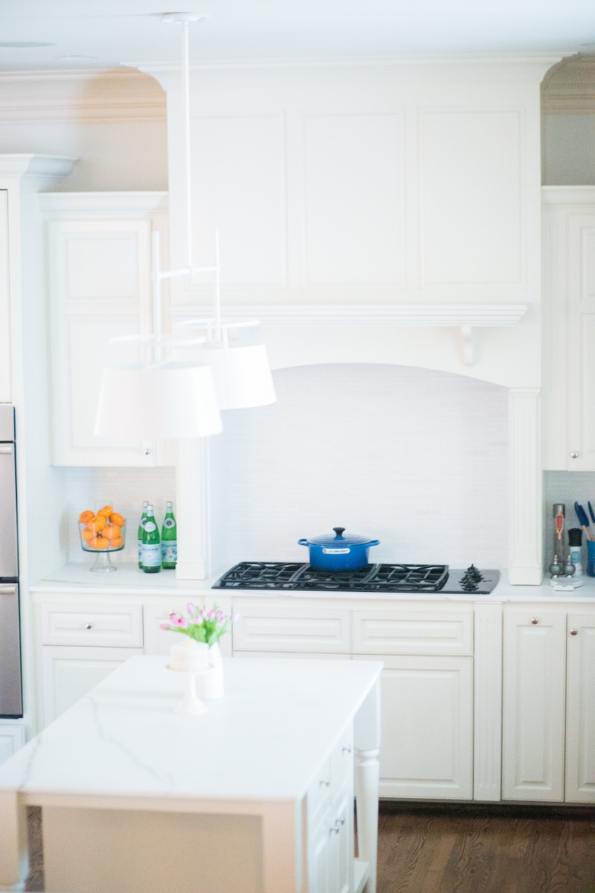 Design Inspiration in all White Kitchen with White Urban Electric Light Fixture with Pops of Color Against the Marble and White Cabinetry on Fashionable Hostess