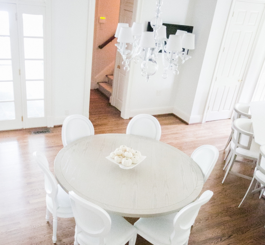 Round Grey Kitchen Table with White Chairs and Serena and Lilly Clear Light Fixture in White Kitchen on Fashionable Hostess