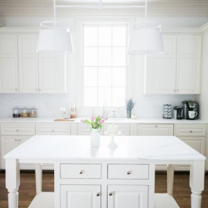 Gorgeous White Marble Island with Light Fixture by Urban Electric Above Amazing Light from Window above Farm Sink on Fashionable Hostess.jpg2