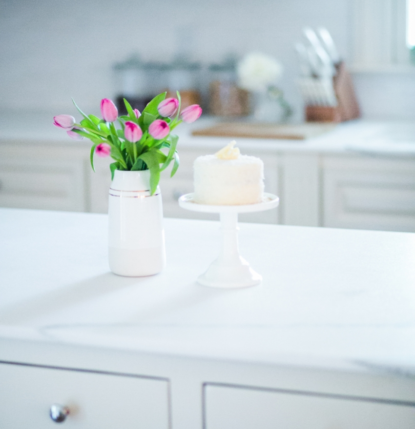 White Kitchen with Marble Island and Coconut Cake on White Cake Stand on Fashionable Hostess